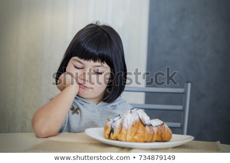Cute black hair little girl looking at croissant Stock photo © boggy
