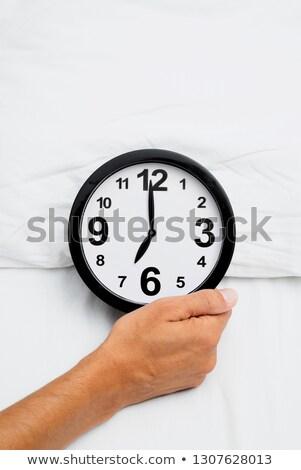 man grabbing a clock at seven in bed Stock photo © nito