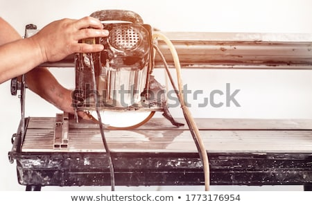 Сток-фото: Worker Using Wet Tile Saw To Cut Wall Tile At Construction Site