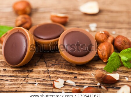 box of homemade candies on wooden background with mint and nuts a hazelnut in caramel and chocolate stock photo © denismart