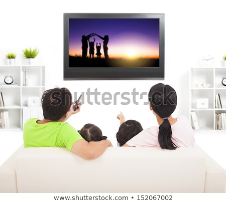Young woman watching television sitting on the sofa at home. Back view Stock photo © Lopolo
