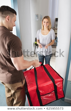 Happy pizza delivery man with food parcels Stock photo © Kzenon