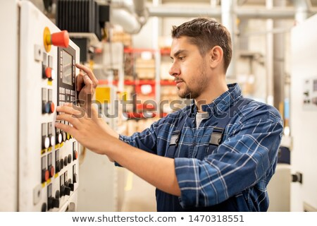 Contemporary engineer of large industrial plant adjusting settings of machinery Stock photo © pressmaster