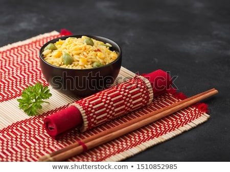 Black bowl with boiled organic basmati vegetable rice with wooden chopsticks on red bamboo placemat. Stock photo © DenisMArt