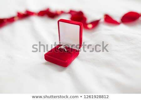 diamond ring in red velvet gift box on bed sheet Stock photo © dolgachov