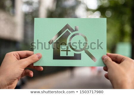 Hands Holding Paper With Cutout House And Loupe Stock photo © AndreyPopov