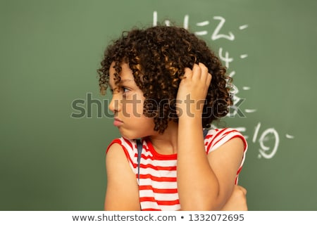 Front view of a thoughtful mixed-race schoolgirl holding her head and standing against the green boa Stock photo © wavebreak_media