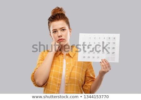 sad red haired teenage girl with calendar sheet Stock photo © dolgachov
