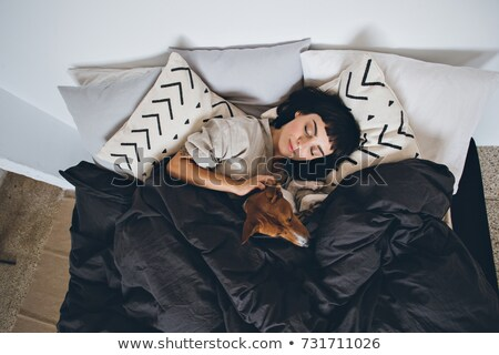 Girl and her dog sleeping together on a bedroom Stock photo © Lopolo