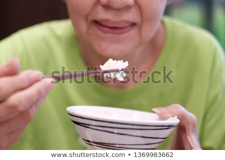 Portrait female eating, using chopsticks holding rice bowl, in r Stock photo © Lopolo