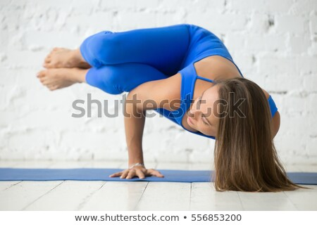 Young attractive woman practicing yoga doing side crane pose in dark room Stock photo © GVS