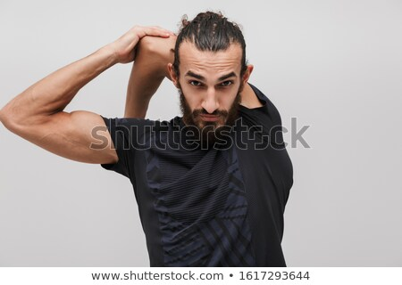 Image of handsome brunette sportsman wearing tracksuit doing wor Stock photo © deandrobot