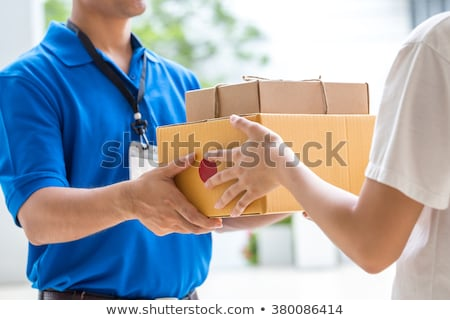 Woman accepting boxes from courier. Stock photo © choreograph