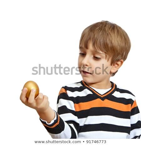 Boy holding a golden easter egg Stock photo © lovleah