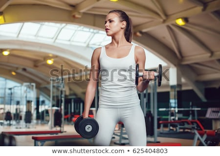 Portrait of sporty girl in tank top with dumbbell Stock photo © pekour