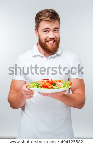 young man with plate of fresh healthy vegetables stock photo © tarikvision