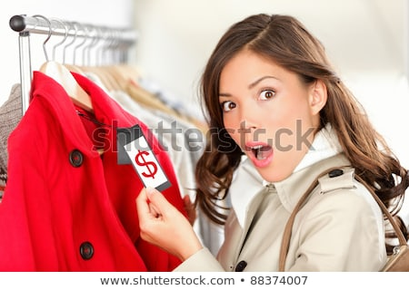 Woman holding price tag in clothing store Stock photo © deandrobot