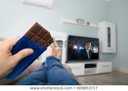 man eating chocolate while watching television stock photo © andreypopov