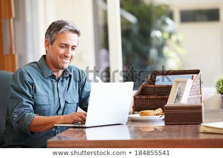 Dojrzały mężczyzna za pomocą laptopa biurko domu działalności komputera Zdjęcia stock © Lopolo