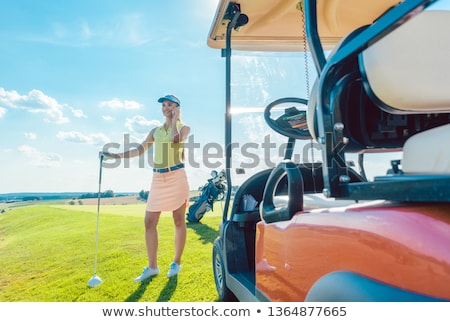 Сток-фото: Cheerful woman talking on mobile phone on the golf course