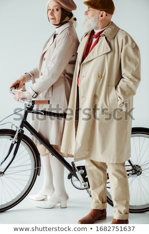 senior woman on the side of a bike in studio white background stock photo © lopolo