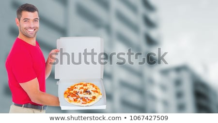 Stock photo: Delivery man with pizza against blurry office