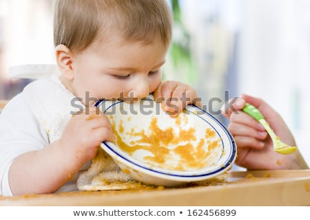 Stock photo: Sweet messy baby boy biting plate after eating the food.