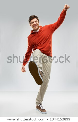happy young man in hoodie stepping up Stock photo © dolgachov