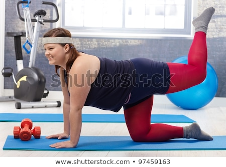 photo of young caucasian woman doing exercise with dumbbell stock photo © deandrobot