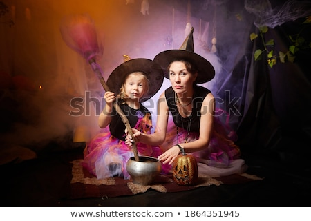 Young beautiful witch with black magic pot and magic hat and bla Stock photo © bluering