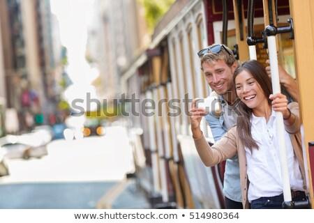 San Francisco city tourists riding cable car tramway tourism people lifestyle. Young interracial cou Stock photo © Maridav