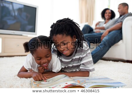 Smiling young boy lying with book in living room stock photo © get4net