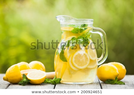 pitcher of cool lemonade with glass on table stock photo © sandralise