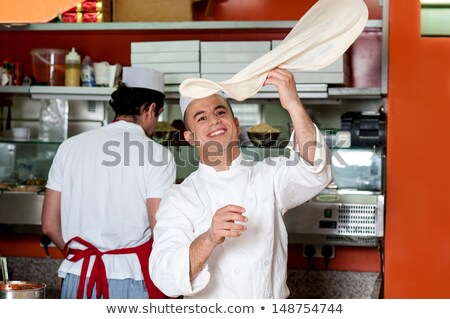 Chef throwing the pizza base dough Stock photo © stockyimages