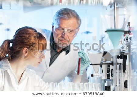 Young scientist pipetting red solution. Stock photo © kasto