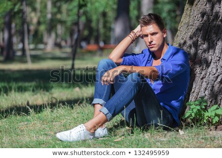 casual man looking down while leaning on a tree Stock photo © feedough