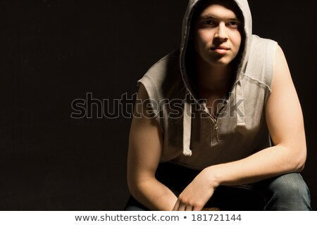 Portrait of a pensive muscular man with arms folded leaning on the wall Stock photo © deandrobot