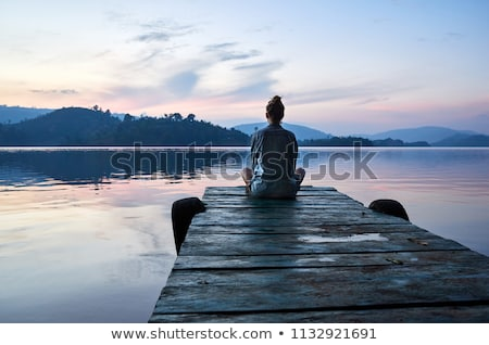 serene view of calm lake and tree silhouettes stock photo © juhku