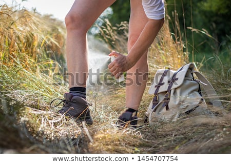 Woman spraying mosquito repellent on leg skin Stock photo © Maridav