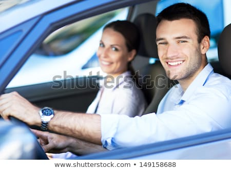 Stock photo: Smiling excited couple sitting inside a new car