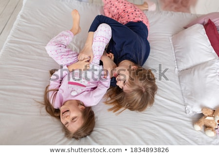 Girl and woman lying in bed tickling Stock photo © IS2