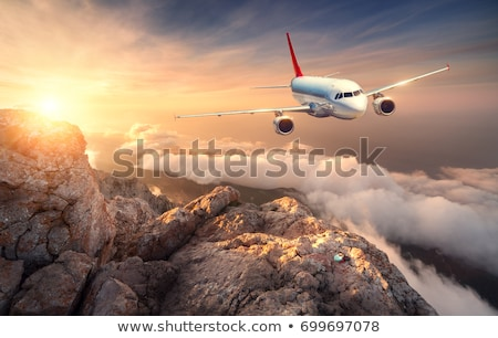 Airplane is flying over rocks and clouds at sunset Stock photo © denbelitsky