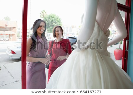 Mother and daughter looking at wedding dress in shop window Stock photo © IS2