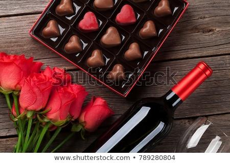 Roses rouges bouteille de vin chocolat boîte saint valentin table en bois Photo stock © karandaev