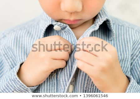 Boy getting dress by himself Stock photo © colematt