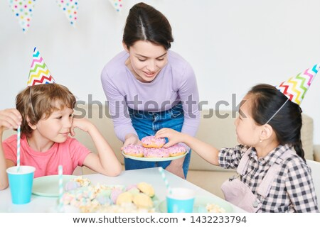 Little girl in birthday cap taking donut from plate held by mother Stock photo © pressmaster