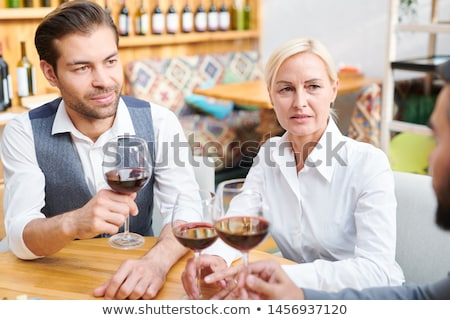 Group of colleagues in formalwear discussing quality of red wine Stock photo © pressmaster