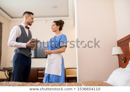 Young elegant porter with touchpad looking at pretty chamber maid in uniform Stock photo © pressmaster