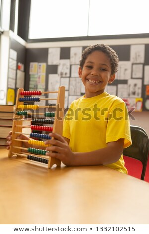 Front view of happy smiling mixed-race schoolboy with abacus looking at camera in a classroom at ele Stock photo © wavebreak_media