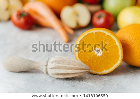 Sliced orange and wooden squeezer against blurred fruit and vegetables background. Squeezing of fres Stock photo © vkstudio